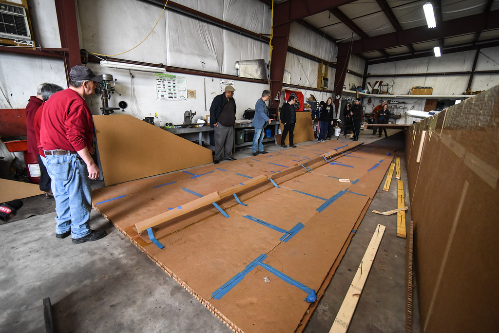 ". A crew of people prep the top wing for installation during a ""Meet the Plane\"" media event held by  Project Soar at the Fitchburg Municipal Airport on Saturday.  SENTINEL & ENTERPRISE JEFF PORTER"