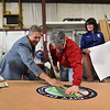 """Jeff Beck (left) and Karin Gaffney (right) watch at Fitchburg mayor Stephen DiNatale applies a Fitchburg seal to a 64 foot paper airplane during the """"Meet the Plane"""" media event held by  Project Soar at the Fitchburg Municipal Airport on Saturday.  SENTINEL & ENTERPRISE JEFF PORTER"""