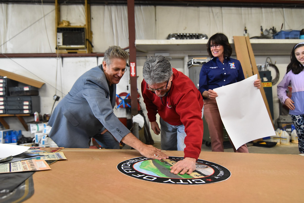 ". Jeff Beck (left) and Karin Gaffney (right) watch at Fitchburg mayor Stephen DiNatale applies a Fitchburg seal to a 64 foot paper airplane during the ""Meet the Plane\"" media event held by  Project Soar at the Fitchburg Municipal Airport on Saturday.  SENTINEL & ENTERPRISE JEFF PORTER"