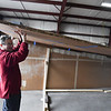 """Daron Massey of Lunenburg assists in installing the top wing to a giant 64 foot paper airplane during a """"Meet the Plane"""" media event held by  Project Soar at the Fitchburg Municipal Airport on Saturday.  SENTINEL & ENTERPRISE JEFF PORTER"""
