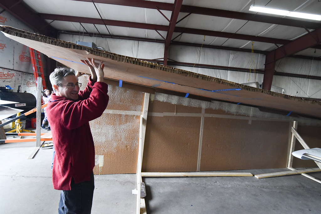 ". Daron Massey of Lunenburg assists in installing the top wing to a giant 64 foot paper airplane during a ""Meet the Plane\"" media event held by  Project Soar at the Fitchburg Municipal Airport on Saturday.  SENTINEL & ENTERPRISE JEFF PORTER"