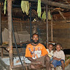 Inside a home in Paru village. The square structure behind the father is the firepit/stove.