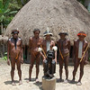 Some village tribesmen with mummy. Men adorned with feathers and traditional Dani Tribal Penis Gourds. Baliem Valley