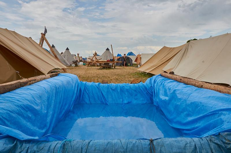 La piscine construite en perche et brelage d'une caravane