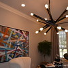 October 23, 2016<br /> <br /> ASHTON ABBEY<br /> <br /> NOTE: This is one of my favorite rooms in the home. I love this artsy ceiling light and wall art in a room to the right of the entry/foyer of the home!<br /> <br /> As its name would imply, Ashton Abbey is a spectacular home with such a feeling of space, timelessness and grandeur that the technology and modern features incorporated into the construction almost become a reminder that it is, indeed, 2016.<br /> <br /> Designed and built with the today's on-the-go family in mind, Ashton Abbey is a 5224 square foot, two-story home situated on an estate lot. Step through the front door into a two-story foyer which extends to the two-story living room and right away you'll realize that this is an exceptional home.<br /> <br /> Encompassing four spacious bedrooms, four full bathrooms and two half-baths, Ashton Abbey boasts a Professional-style kitchen equipped with GE Monogram appliances. Off the kitchen is a large walk-through in which you'll find a built-in wet bar and a generous pantry. The kitchen looks out into the vaulted gathering room which is highlighted by one of the home's three fireplaces. The vaulted porch with its beautiful cedar work is just one of the impeccable exterior features of this home. <br /> <br /> Ashton Abbey boasts two double-car garages as well as a porte cochere. Escape from the main living spaces into the relaxing retreat of a spacious and well-appointed master bedroom, where you'll find not only a large bath with a walk-through shower and free-standing bathtub, but also an oversized master closet for him and her that connects to the laundry room for easy and convenient access.<br /> <br /> Upstairs in Ashton Abbey there are two bedrooms with private baths as well as a media room with the latest in technology and a playroom featuring a balcony overlooking the great room downstairs.<br /> Whether you are looking to entertain or be entertained, no detail has been overlooked in designing th