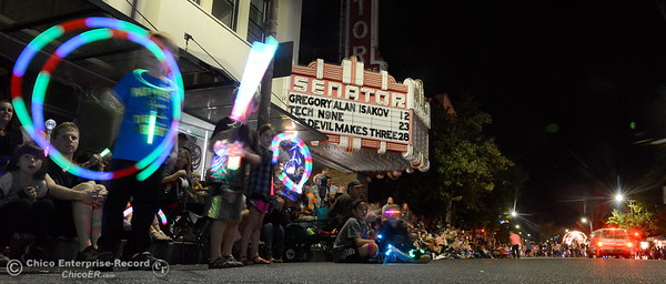 "Children twirl glow sticks as floats go by the Senator Theater during the 29th annual Parade of Lights Friday Oct. 13, 2018. The theme of ""Exploration: From Deep Sea to Deep Space (and everything in between!),"" was evident as spacemen and undersea creatures made their way down Main Street.  (Bill Husa -- Enterprise-Record)"