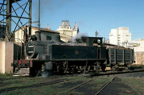 Ferrocaril Presidente Carlos Antonio Lopez No 4, Asuncion, Paraguay, 19 October 1976 1.  The standard gauge wood-burning 2-6-2T takes water at the loco shed turntable.  It was built by Hawthorn Leslie 2815 / 1910.  No 4 has since been scrapped, but in 2009 identical FPCAL Nos 2 and 5 (Hawthorn Leslie 2809 / 1910 & 2977 / 1914) were reported dumped at Sapucai.  Beyond the loco are the turrets of San Francisco station, seen in subsequent views.  Photo by Les Tindall.
