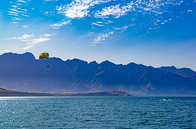 Parasailing, two man group, over Lake Wakatipu and the Southern Alps, Kā Tiritiri o te Moana, Queenstown, New Zealand, sports, things to do, things to see. Parasailing wing with blue skyline and Southern Alps background. Boat in lake Wakatipu.