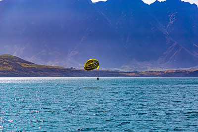 Parasailing, two man group, over Lake Wakatipu and the Southern Alps, Kā Tiritiri o te Moana, Queenstown, New Zealand, sports, things to do, things to see. Parasailing wing with blue skyline and mountain background.
