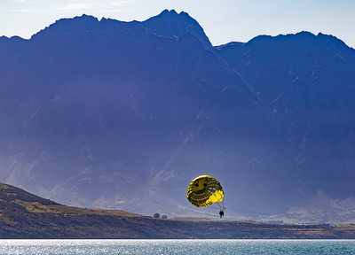 Parasailing, two man group, over Lake Wakatipu and the Southern Alps, Kā Tiritiri o te Moana, Queenstown, New Zealand, sports, things to do, things to see. Parasailing wing with blue skyline background.