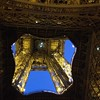 Looking up through the Eiffel Tower at night.