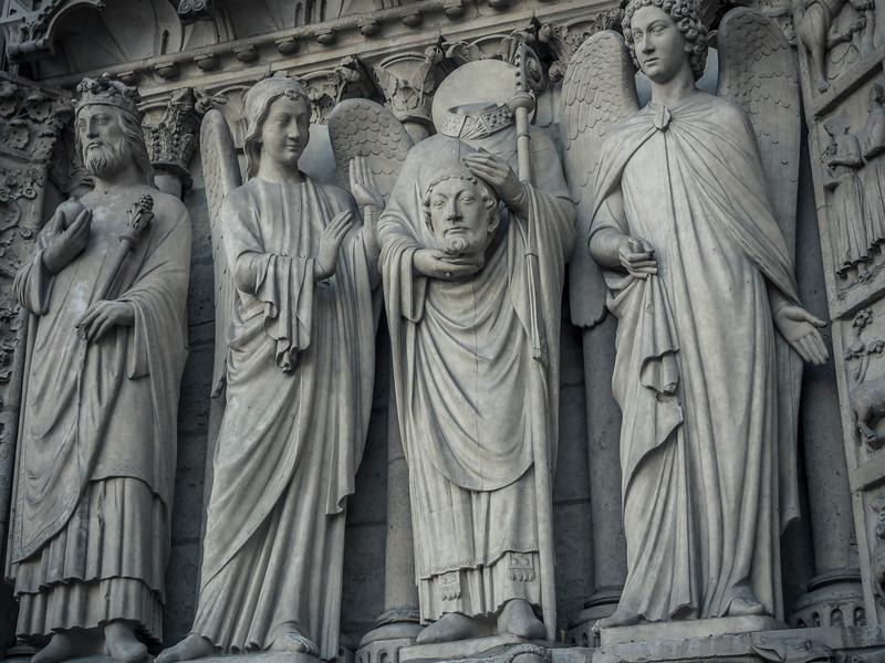 Saint Denis sculpture above door at Notre Dame