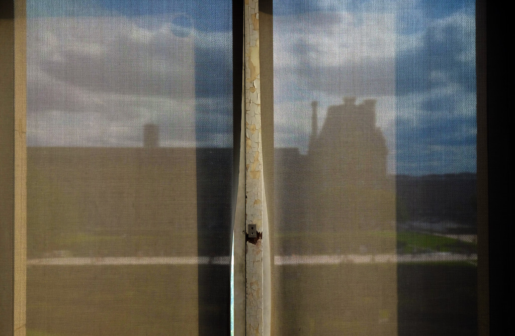 . The Louvre seen through curtains at Musée des Arts Décoratifs in Paris. Photo by Shmuel Thaler