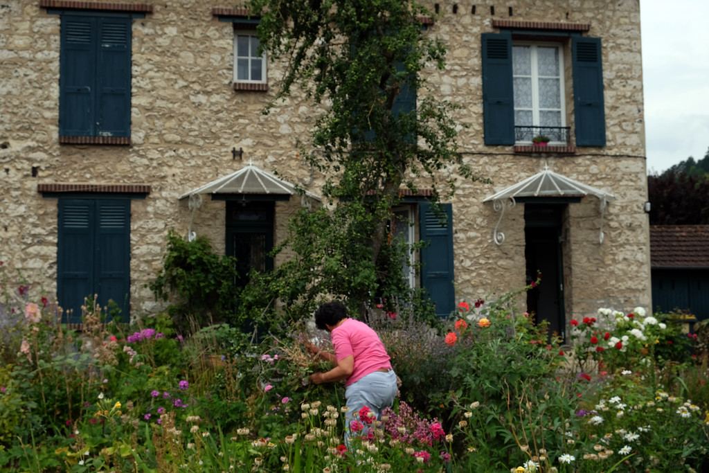 . A woman tends to the flowers in her garden in in Giverny, France, a few houses away from the home, garden and lily pond where Claude Monet lived from 1883 to 1926. Photo by Shmuel Thaler