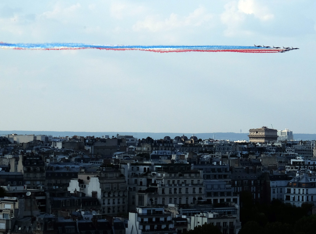 . French Air Force pilots streak the sky with the tri-colors as the French national soccer team marches in a celebratory parade after winning the World Cup. Photographed from the Eiffel Tower. Photo by Shmuel Thaler