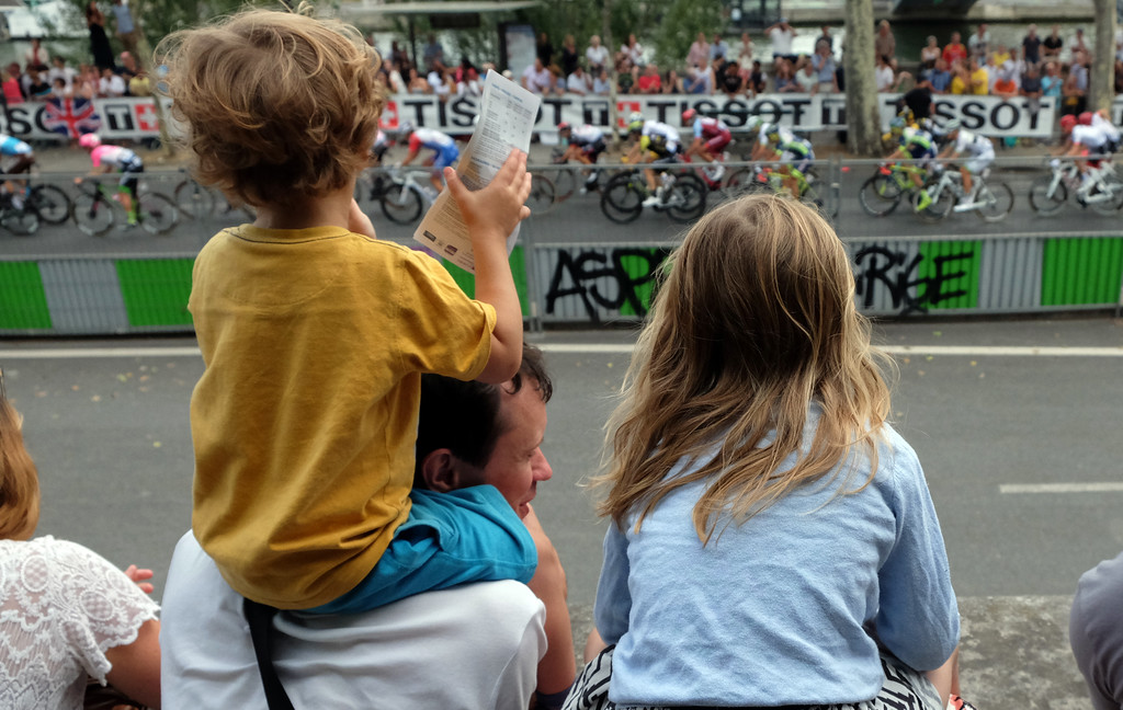 . Two young spectators watch the Tour de France riders race along Quai François Mitterrand in Paris during the final stage of the bike race. Photo by Shmuel Thaler