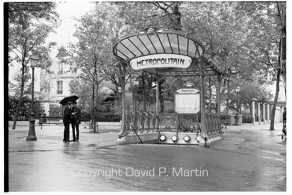 At the Metro stop Abbesses. The station's entrance, which was designed by Hector Guimard, is one of only two original Guimard entrances left in Paris. This entrance was originally used for the Hôtel de Ville metro station, but was moved to its current location in 1970.