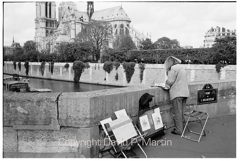 An artist on the Pont de L'Archeveche.