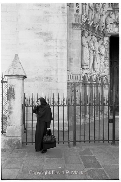 A nun calling home in front of Notre Dame?