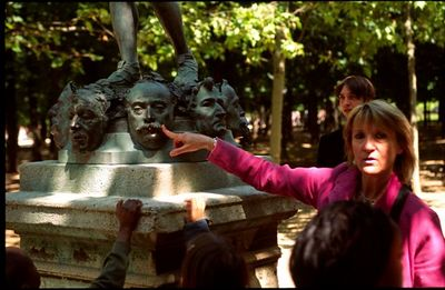 Teacher explains the faces on the statue, Jardin du Luxembourg
