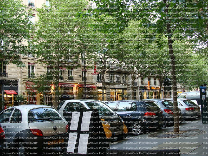 Eating at a side walk café in Paris, smart cars parked straight  into the sidewalk