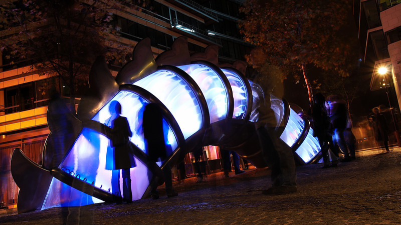 Sort of a fountain, created by the chinese artist Chen Zhen. It's a dragon, that surfaces on a square in Paris, surrounded by very recent buildings close to quai d'Austerlitz. The Inside of the dragon is illuminated in changing colors and there's water flowing....