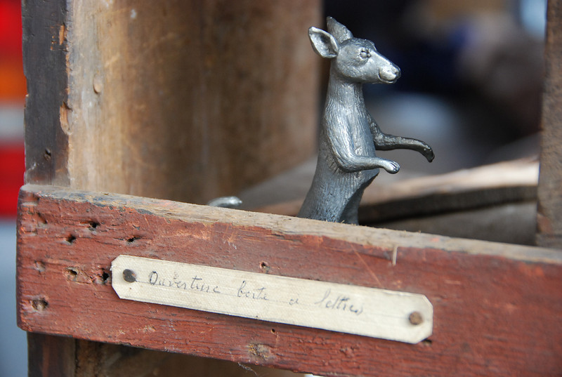 Metal figure of dog on hind legs in letter box. Porte de Clignancourt Flea Market, Paris, 2011.