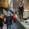 France, Paris (75), Jardin d'Erivan, Pont Alexandre III, Artiste à vélo se balade// France, Paris, Erivan gardens along the Seine, a bicycle rider is observed by a couple on their afternoon stroll