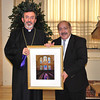 Photographer Armen James Ghugasian presents Archbishop Barsamian with a framed photograph of stained glass windows at Holy Trinity Church.
