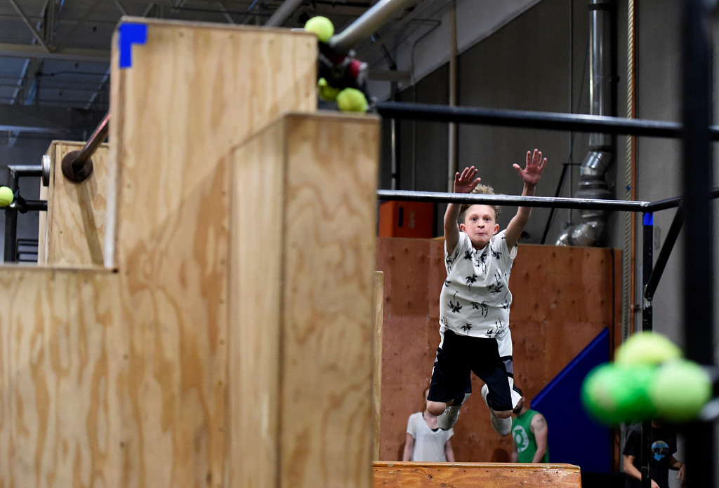 . Will Dennis leaps to a cross bar during an adult Parkour class on Friday at Apex Louisville. For more photos of the workout class go to dailycamera.com Jeremy Papasso/ Staff Photographer 06/22/2018