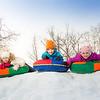 Row of children sliding down on the tubes