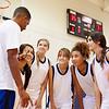 High School Basketball Team Having Team Talk With Coach