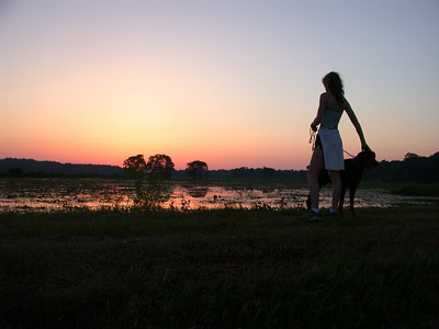 "19 May 2002: We'd run an Alford Greenway Park loop, and needed a little ""tack-on"" distance. Here, as we finish our Cadillac tack-on, Lori and Panzer enjoy the sunset from the Second Levee."