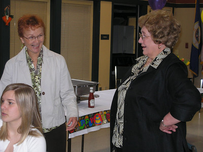 Vadis and Barbara enjoying a conversation; Kelly in front