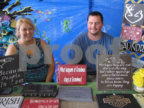 Kelli and Shawn George of S & K Creations displaying their handmade signs.