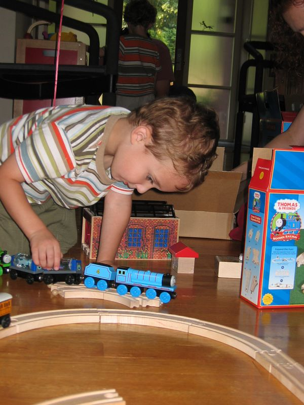 Charles plays with new trains on new tracks.