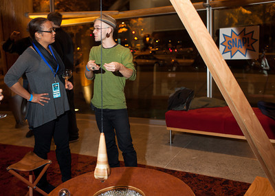 """Jeramie Bellmay (R) explains his installation """"The Scoposcope"""" to Margaret Johnson at the DC Week closing party at the Arena Stage in Washington, DC. Photo by Dakota Fine."""