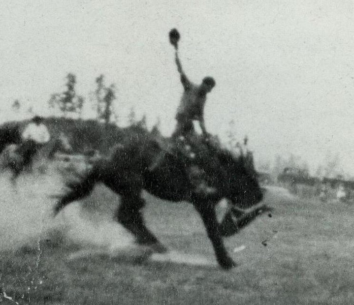 """Floyd riding one of his spectacular saddle-bronc rides, """"fanning"""" his horse with his hat."""