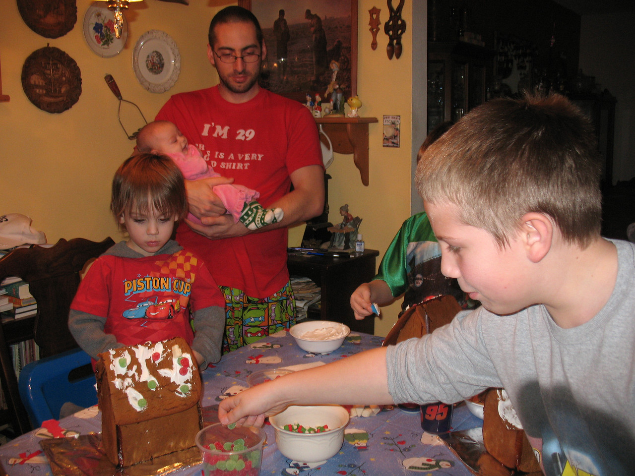 Link and Andrew decorating their Gingerbread houses as Jeremy and Nikola watch.