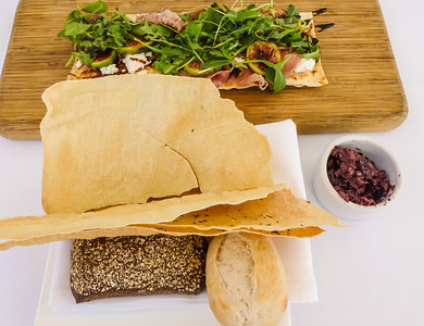 Flatbread appetizer made with prosciutto, roasted pears, brie, fig jam, arugula at The Restaurant