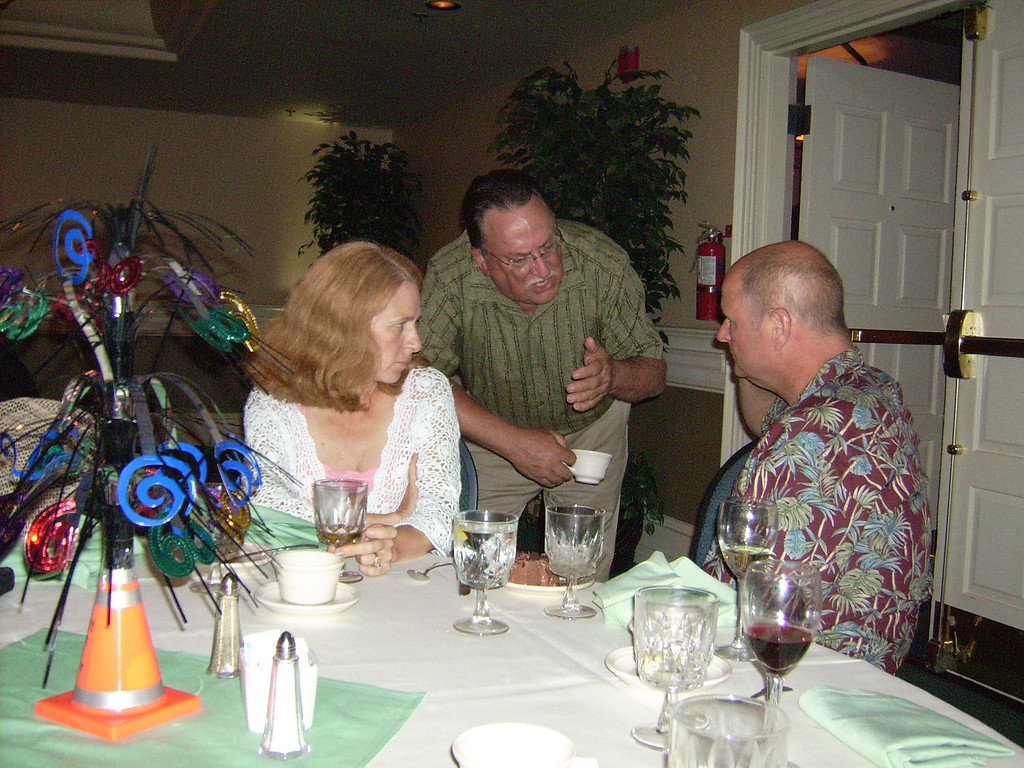 Jim Robertson with Kathy and Mark Glasmeier.  (You couldn't be talking 'ski club shop' at Larry's party could you? :)