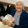 Marguerite Wabano holdings gifts of cash recieved on her 103rd birthday.