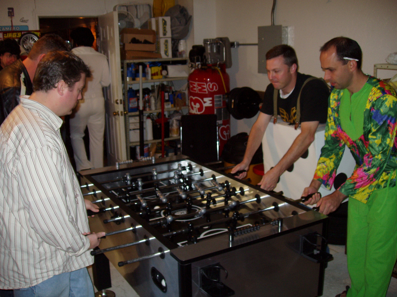 "Terry ""No Costume Lamer"" Fair, Jeff ""Sonny"" Lathan, Lucky Duck, Justin playing foosball"