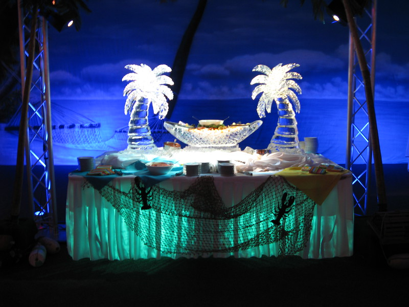 Beach Themed Birthday- The ice carving of palm trees holding a hammock is filled with shrimp.  The table is lighted from above as well as underneath. The beach backdrop in the background highlights the ice and the fisherman's net on the front helps to carry the theme.  Ice carving by Ice Matters. Lighting by Awesome Audio.<br /> Maneeley's in South Windsor