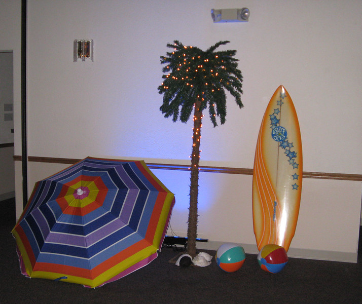 Beach Birthday Party- A colorful beach umbrella, lighted palm tree, surfboard, conch shells, beach balls, and blue uplighting decorated the space in front of the bar.<br /> Maneeley's in South Windsor