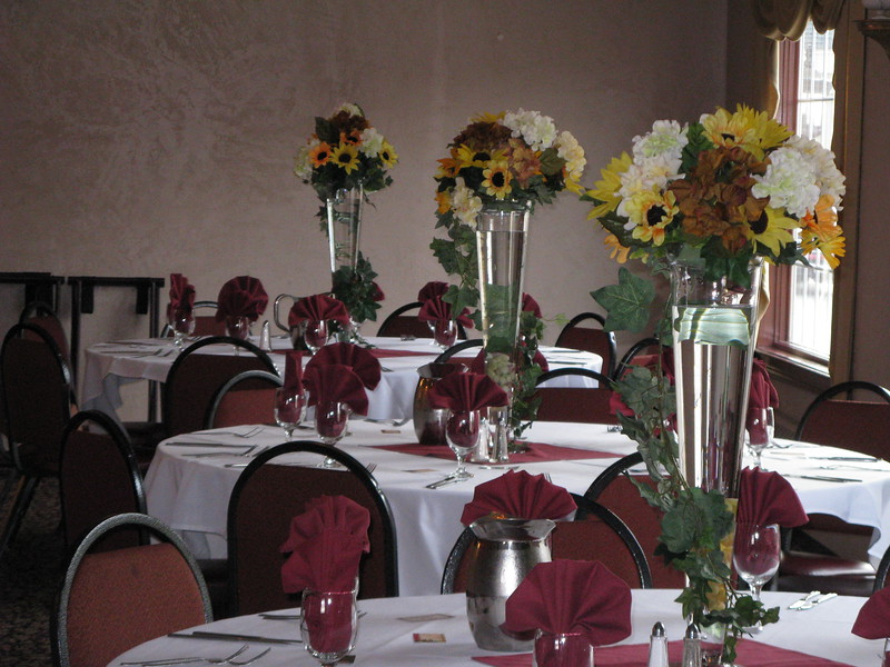Under the Tuscan Sun- Sunflower Silk Floral Arrangements were placed on vases filled with water and grapes.  The arrangements added drama and height but did not block the view!  The ivy trailed down the side of the vase.  Burgundy napkins carried the wine color theme. <br /> Georgina's in Bolton, CT