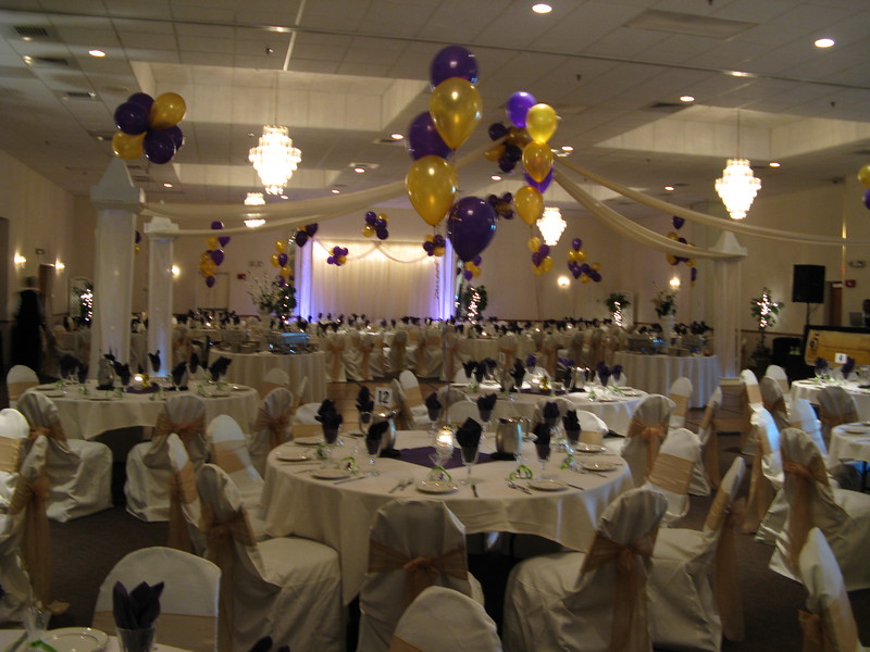 Purple and Gold Prom- Dance canopy with castle tops and purple and gold balloons on every table.  This prom had 40 tables.  The ivory chaircovers and gold organza bows really made the prom look formal.  The napkins and centers were purple.  The lobby had a purple and gold balloon arch with a red carpet to lead the guests into the breathalyzer station. <br /> Maneeley's in South Windsor