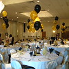 Graduation Party-  The guest of honor graduated from Bryant University.  Their colors are black and gold, so we put sprays of balloons on every table.  The ivory chaircovers with gold organza bows dressed up this special occasion.  <br /> Maneeley's in South Windsor