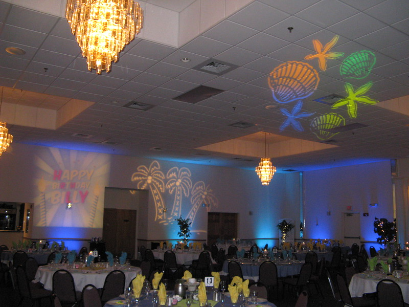 Beach Birthday Party- Another shot of the room with the teal and blue uplights and the colored shells and palm trees on the wall and ceiling. Lighting by Awesome Audio.<br /> Maneeley's in South Windsor
