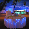 Beach Birthday Party- Here's a great example of 2 kinds of under table lighting.  The table in the front is under lighted with blue LED string lights.  The table in the back is under lighted with 2 PAR 250 cans.  The table in the front is done with about $15 worth of lights.  The table in the back has about $400 worth of lights underneath.  The beach backdrop we rented and we rented the palm trees to cover the light towers that are highlighting the top of the table and the backdrop.  Cabaret tables allow guests to set down their drinks and appetizers as they mingle.<br /> Maneeley's in South Windsor. CT